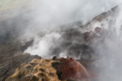 Aerial photography of smoking volcano, taken from an open-door helicopter flying over the Big Island of Hawaii. Photo by Alina Oswald.