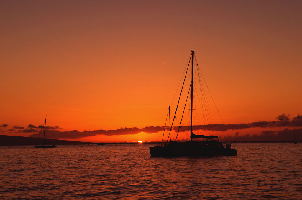 Sailing boat silhouetted by sunset light. Somewhere between the islands of Lanai and Maui, Hawaii. Photo by Alina Oswald.