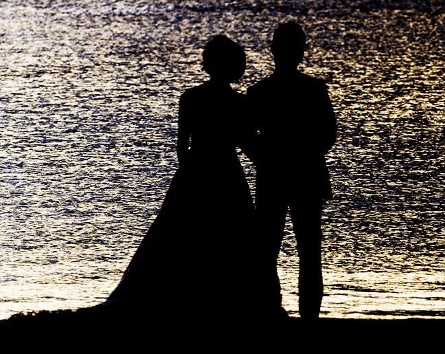 Destination weddings. Newlyweds watch the sunset on the beach. Photo by Alina Oswald.