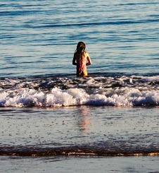 Young woman breaking through waves, facing the vast unknown and ocean ahead of her.