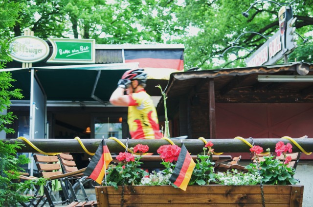Biker sporting German glad colors rides by the Biergarten in Grunwald, Berlin, Germany