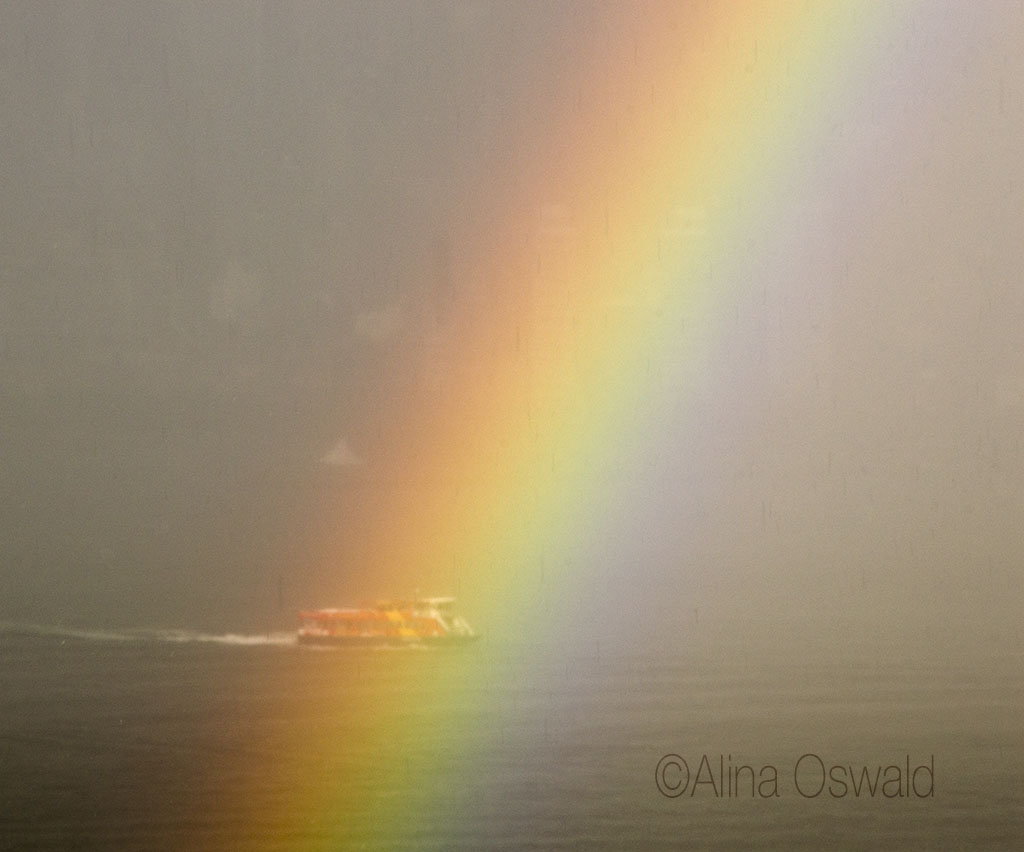 Ferry sailing down the Hudson, through the rainbow. Photo by Alina Oswald.