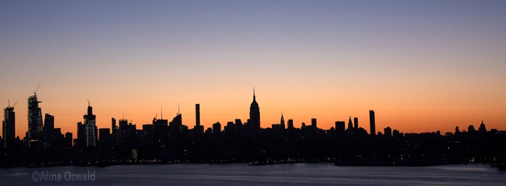 Sunrise light silhouettes Manhattan skyline. Photo ©Alina Oswald. All Rights Reserved.