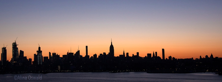 Sunrise light silhouettes Manhattan skyline. Photo ©Alina Oswald. All Rights Reserved.