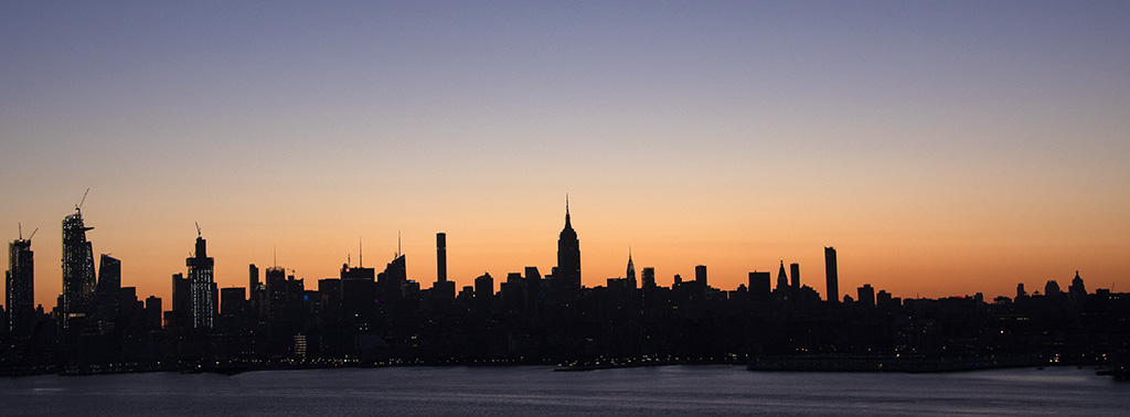 Pano view of NYC silhouetted by sunrise light. Photo by Alina Oswald. All Rights Reserved.