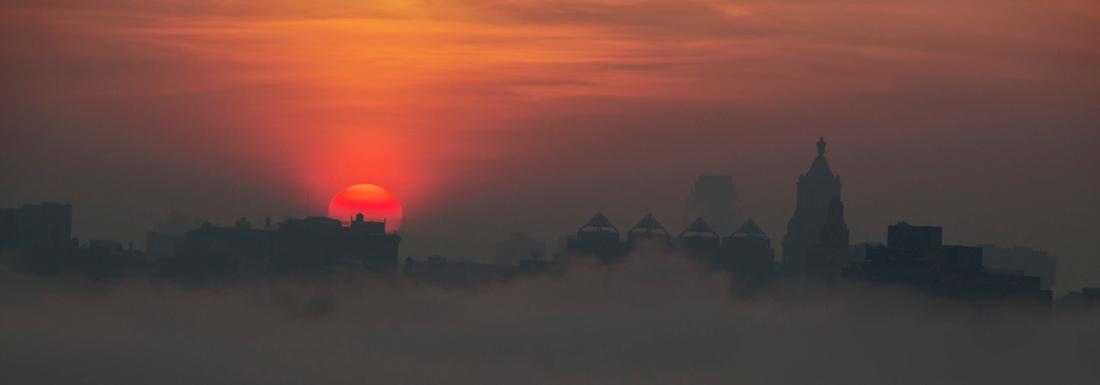 Sunrise Fog hangs low over Manhattan skyline. Photo by Alina Oswald.