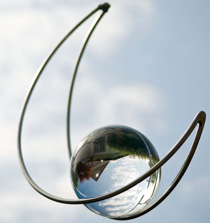 Frisian house reflected in glass ball ornament, in Sylt, Germany. Photo by Alina Oswald.
