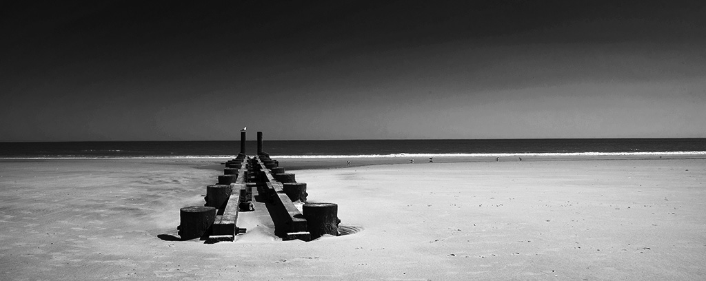 Lonely pier on Atlantic City beach. B&W photo by Alina Oswald. All Rights Reserved.